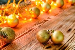 El fondo de la Navidad con las bolas y brillar intensamente del juguete se enciende en de madera Imagen de archivo libre de regalías
