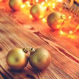 El fondo de la Navidad con las bolas y brillar intensamente del juguete se enciende en de madera Fotografía de archivo