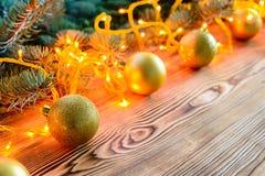 El fondo de la Navidad con las bolas y brillar intensamente del juguete se enciende en de madera Foto de archivo