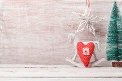 El fondo de la Navidad con las decoraciones rústicas, el caballo mecedora, el árbol de pino y el corazón forman Foto de archivo libre de regalías