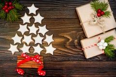 El fondo de la Navidad con las galletas, los presentes y el abeto del pan de jengibre ramifica en el viejo tablero de madera Foto de archivo libre de regalías