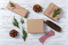 El fondo de la Navidad con la mano hizo los regalos a mano, presentes en la tabla de madera rústica La Navidad o embalaje del Año Fotografía de archivo