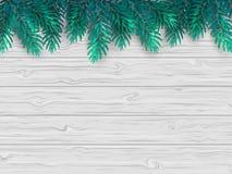 El fondo de la Navidad o del Año Nuevo con el abeto realista ramifica en una tabla blanca de madera Foto de archivo libre de regalías