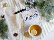 El fondo de la Navidad y del Año Nuevo con el saludo da la nota de las letras y la taza de té Fotografía de archivo