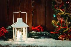 El fondo de la Navidad y del Año Nuevo con la Navidad mira al trasluz la linterna y las ramas de árbol de navidad, nieve y las de Foto de archivo libre de regalías