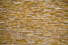 El fondo de la pared, alineado con el fondo del artificThe de la pared, aline? blanco rectangular de la piedra ial y amarillo irr fotografía de archivo libre de regalías