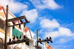 El fondo de los posts de la electricidad y del cielo azul de las casas urbanas En el fichero de Fotos de archivo