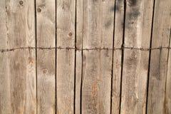 El fondo de los tableros grises de la cerca con los nudos martilló el alambre de púas del metal fotos de archivo
