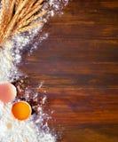 El fondo de madera derramó la harina y el huevo con la yema de huevo cerca de tallos del trigo Foto de archivo