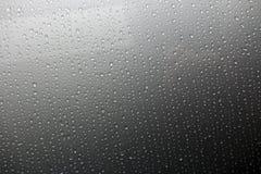 El fondo de una gota de la lluvia gotea abajo del vidrio Foto de archivo libre de regalías