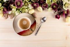 El fondo del café con los huevos y la primavera de Pascua florece sobre la madera Imagen de archivo