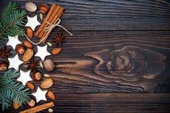 El fondo del día de fiesta de la Navidad con las galletas y el abeto del pan de jengibre ramifica en el viejo tablero de madera C Fotos de archivo