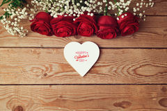 El fondo del día de tarjeta del día de San Valentín con las rosas rojas y el corazón forman en la tabla de madera Visión desde ar Fotos de archivo libres de regalías