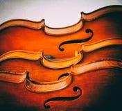 El fondo del diseño del arte abstracto de los violines apilados a bordo, parte delantera de la demostración media del violín, en  foto de archivo
