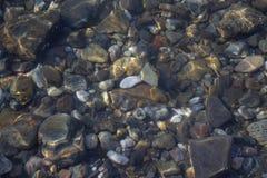 El fondo del mar de guijarros coloreados cerca de la orilla imagenes de archivo