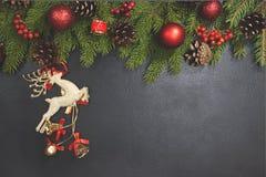 El fondo del marco de la Navidad de conos del pino del árbol de Navidad, la bola roja, los ciervos en la tabla negra y el espacio Imágenes de archivo libres de regalías