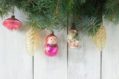 El fondo del ` s de la Navidad o del Año Nuevo con las ramas del abeto y el árbol de navidad viejo juega en un fondo blanco Fotos de archivo libres de regalías