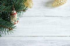 El fondo del ` s de la Navidad o del Año Nuevo con las ramas del abeto y el árbol de navidad viejo juega en un fondo blanco Imagen de archivo