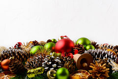 El fondo del saludo de la Navidad con la mano adornó conos del pino Foto de archivo libre de regalías
