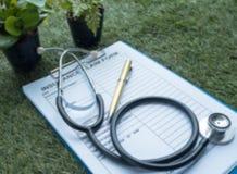 El fondo ligero borroso del diseño del estetoscopio y de la forma de demanda de seguro puestos en la planta de la hierba verde imágenes de archivo libres de regalías