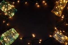 El fondo mágico del tema de la Navidad, floreros del vintage llenó de las luces de la guirnalda, fondo oscuro Visión superior, es Imagen de archivo