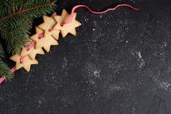 El fondo negro de la Navidad con las galletas y el abeto ramifican Imagen de archivo libre de regalías