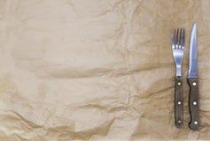 El fondo para el menú Papel de embalaje y una bifurcación y un cuchillo de filete Se utiliza para crear un menú para un asador Fotografía de archivo libre de regalías