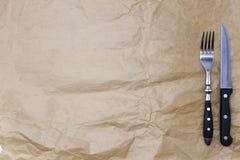El fondo para el menú Papel de embalaje y una bifurcación y un cuchillo de filete Se utiliza para crear un menú para un asador Foto de archivo libre de regalías