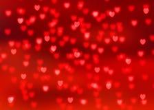 El fondo rojo abstracto con el bokeh en forma de corazón rojo se enciende Foto de archivo