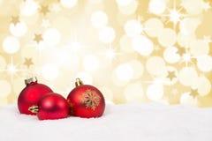El fondo rojo de las bolas de la Navidad protagoniza la tarjeta de oro de la decoración Fotos de archivo libres de regalías