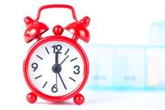 El fondo rojo del despertador y de la caja de la píldora muestra tiempo de la medicina Foto de archivo