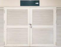 El fondo texturizado puerta de madera blanca vieja del primer con la etiqueta verde dice la manera en la derecha Fotos de archivo libres de regalías