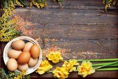 El fondo vacío de Pascua con los huevos y la primavera de Pascua florece Fotografía de archivo
