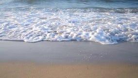 El fondo vacia la arena y las ondas que estrallan en él metrajes
