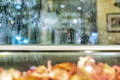 El fondo el vaso de agua está en el vidrio La granulosidad es causada por la lluvia el caer imágenes de archivo libres de regalías
