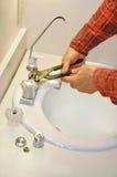 El fontanero aprieta el grifo agujereado Foto de archivo libre de regalías