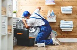 El fontanero del trabajador repara la lavadora en lavadero Imagen de archivo libre de regalías