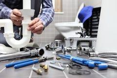 El fontanero en el trabajo en un cuarto de baño, sondeando servicio de reparación, monta fotos de archivo