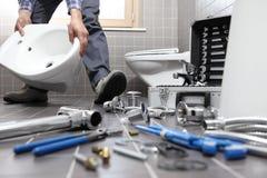 El fontanero en el trabajo en un cuarto de baño, sondeando servicio de reparación, monta imagen de archivo