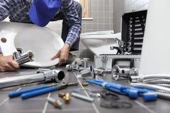 El fontanero en el trabajo en un cuarto de baño, sondeando servicio de reparación, monta foto de archivo