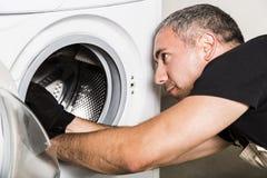 El fontanero en uniforme repara el tambor de la lavadora en lavadero fotografía de archivo