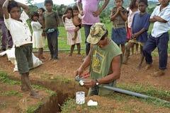 El fontanero está pegando el foso cavado los tubos del PVC Foto de archivo