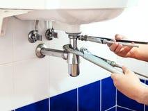 El fontanero fija las tubo-llaves para instalar un sifón fotografía de archivo