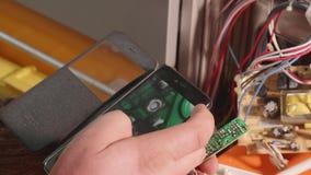 El fontanero utiliza smartphone como lupa para mirar partes de la tarjeta electrónica almacen de metraje de vídeo