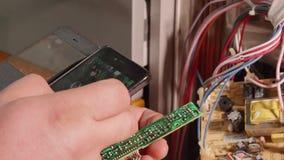 El fontanero utiliza smartphone como lupa para mirar partes de la tarjeta electr?nica metrajes