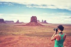 El fotógrafo apto de la hembra toma las imágenes en valle del monumento, los E.E.U.U. Imagen de archivo