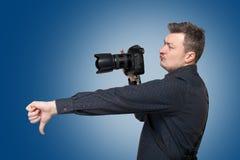El fotógrafo con la cámara digital muestra el pulgar abajo Imagen de archivo