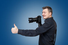 El fotógrafo con la cámara digital muestra el pulgar para arriba Imagen de archivo libre de regalías
