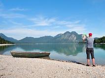 El fotógrafo con el ojo en el visor está tomando la foto del lago con las montañas Fotos de archivo