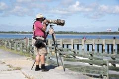 El fotógrafo con una cámara montó en un trípode Fotografía de archivo libre de regalías